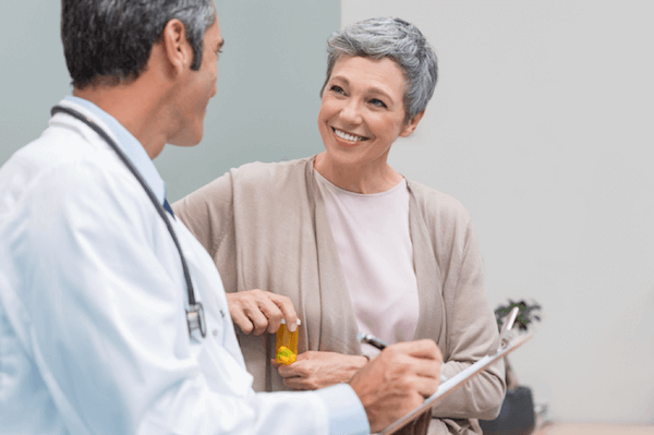 Woman smiles as doctor gives prescription