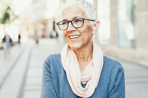 Smiling woman wears glasses and a scarf outdoors