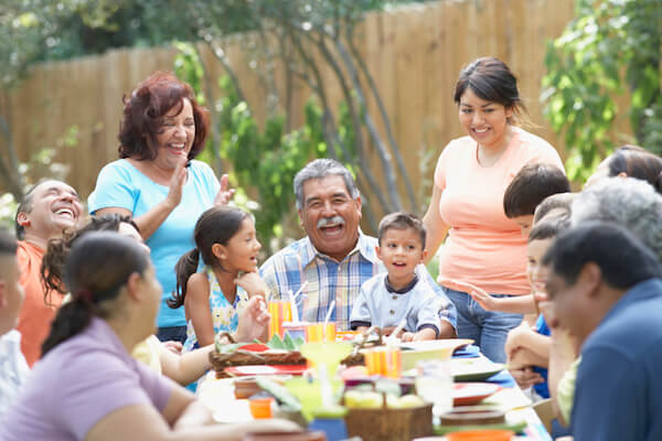 Multiple generations of a large family laugh and enjoy a picnic outdoors