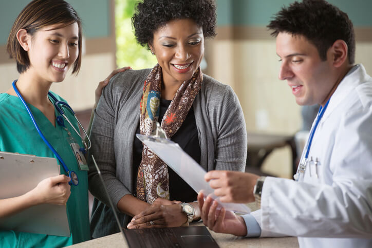 A woman reveiws cost information with her doctor and a nurse