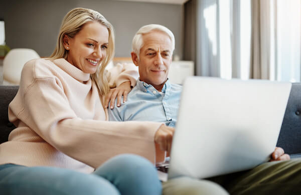 A couple reviews their Medicare enrollment options online on their laptop computer
