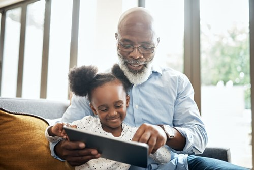 Grandfather and his granddaughter smile as they use tablet computer